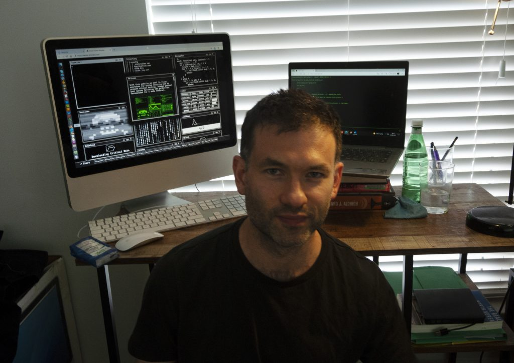 A picture of the author Oliver Harris, in front of a computer.